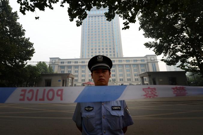 Полицейский стоит напротив здания суда города Цзинань провинции Шаньдун 24 августа 2013 года. Фото: Mark Ralston/AFP/Getty Images