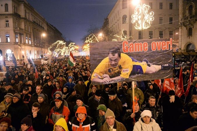 Протестующий держит плакат с текстом «Game Over!», представляющий премьер-министра Венгрии Виктора Орбана как футболиста. Акция протеста направлена против политики Виктора Орбана на сближение с Россией, Будапешт, 2 января, 2014 год. Фото: ATTILA KISBENEDEK/AFP/Getty Images