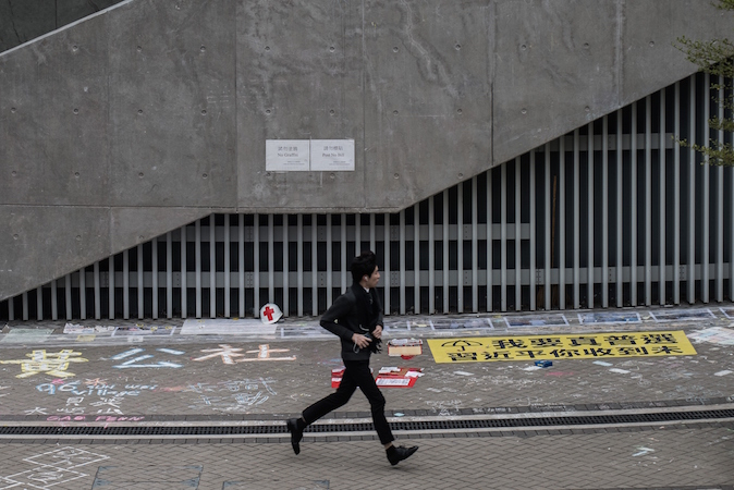 Парень проходит мимо гонконгской «Стены Леннона», расположенной рядом с правительственными офисами, на которой демократические активисты оставляли послания в поддержку протестного движения в Гонконге 5 января 2015. Фото: theepochtimes.com