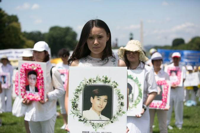 Девушка держит плакат во время митинга в Вашингтоне 17 июля 2014 года. На плакате фото молодого человека, который был замучен до смерти в Китае за приверженность учению Фалуньгун. Фото: Edward Dai/Epoch Times