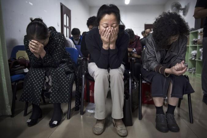 Китайские христиане молятся во время службы в подпольной независимой протестантской церкви в Пекине, 12 октября. В Китае, который официально является атеистической страной, существует много ограничений для христиан, законом разрешены службы только в церквях, одобренных властями. Фото: Kevin Frayer/Getty Images