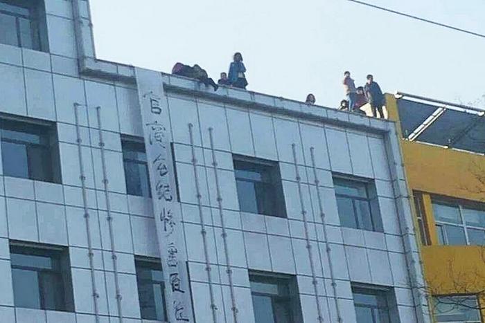 Обманутые вкладчики венчурной компании вывесили плакат и заявили, что совершат самоубийство, если с ними не встретятся чиновники. Город Шочжоу провинции Шаньси. Январь 2015 года. Фото с epochtimes.com
