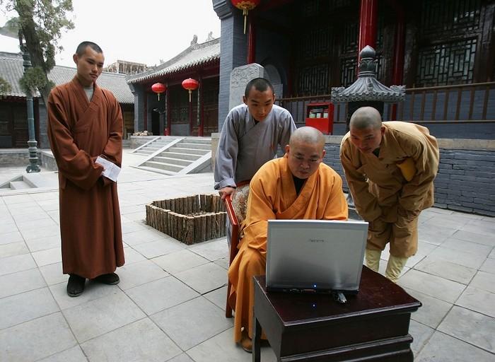 Настоятель монастыря Шоалинь Ши Юнсинь работает за компьютером. Фото: Getty Images