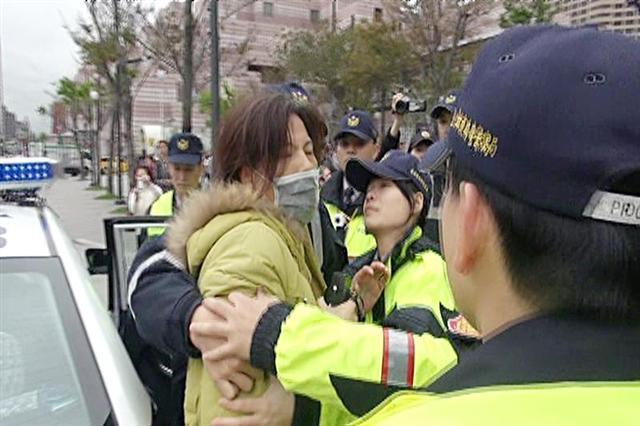 Член прокоммунистической группы Чжан Сюе сопротивляется полиции при аресте. Фото: CNA News
