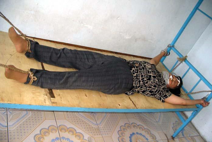 Инсценировка пытки «кровать мертвеца». Фото: minghui.com