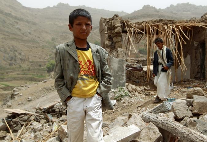 Йеменский мальчик стоит у своего разрушенного авиаударами дома в деревне Бани Матар, расположенной в 70 км от Саны, Йемен, 4 апреля, 2015 год.Фото: MOHAMMED HUWAIS/AFP/Getty Images