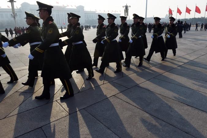 Полиция патрулирует площадь Тяньаньмэнь в Пекине 13 марта 2015 г. Законы в Китае так плохо работают, что криминальные авторитеты сумели наводнить партийные структуры и местные органы власти. Фото: Greg Baker/AFP/Getty Images