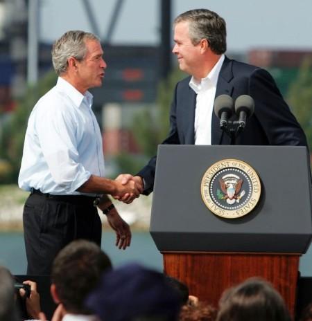 Президент Джордж Буш (слева) и его брат, губернатор Флориды Джеб Буш, пожимают друг другу руки в ходе визита на базу береговой охраны США 31 июля 2006 года. Майами, Флорида. Президент посетил базу в ходе поездки в Майями, где встретился с местными политиками и бизнесменами. Фото: Raedle/Getty Images