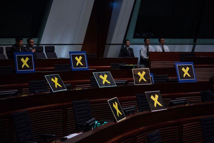 Члены демократической партии Гонконга в знак протеста покинули заседание парламента, оставив на своих местах плакаты с жёлтыми крестами, 22 апреля 2015 года. Фото: Lam Yik Fei/Getty Images