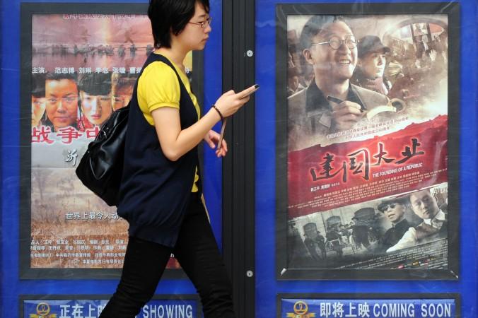 Женщина в Пекине проходит мимо афиши фильма «Основание республики», посвящённого окончанию второй китайско-японской войны. Фото: Frederic J. Brown/AFP/Getty Images