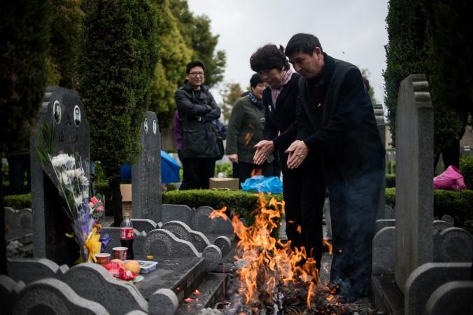 Пара сжигает бумажные деньги на кладбище во время праздника Цинмин в Шанхае 6 апреля 2015 г. Фото: Johannes Eisele/AFP/Getty Images
