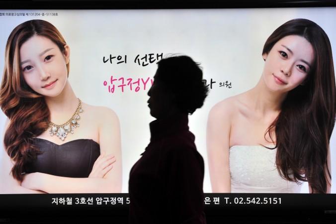 Прохожая идёт мимо рекламы клиники пластической хирургии в Сеуле, Южная Корея, 26 марта 2014 г. Фото: Jung Yeon-Je/AFP/Getty Images