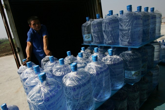 Рабочий грузит бутылки с водой в Сиане, провинция Шааньси, 22 июля 2007 г.  Из 650 000 контейнеров воды, ежедневно продаваемых в Пекине, шестая часть набрана из-под крана. Фото: China Photos/Getty Images