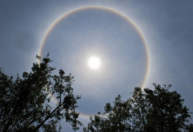 24 мая. Ореол вокруг Солнца  в небе над Мехико 21 мая 2015. Свечение образуется благодаря миллионам крошечных ледяных кристаллов, вызывая рефракцию или расщепление света, а также за счет отражения света от кристаллов льда. Фото: OMAR TORRES/AFP/Getty Images
