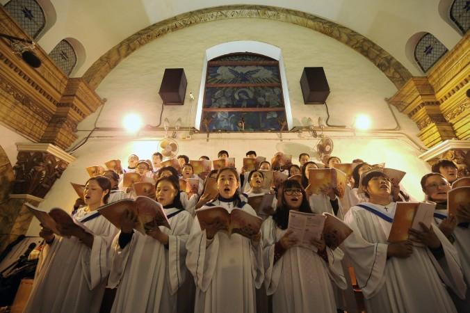 Китайские прихожане поют в канун Рождества в католической церкви в Пекине, 25 декабря 2012 года. Фото: Wang Zhao/AFP/Getty Images