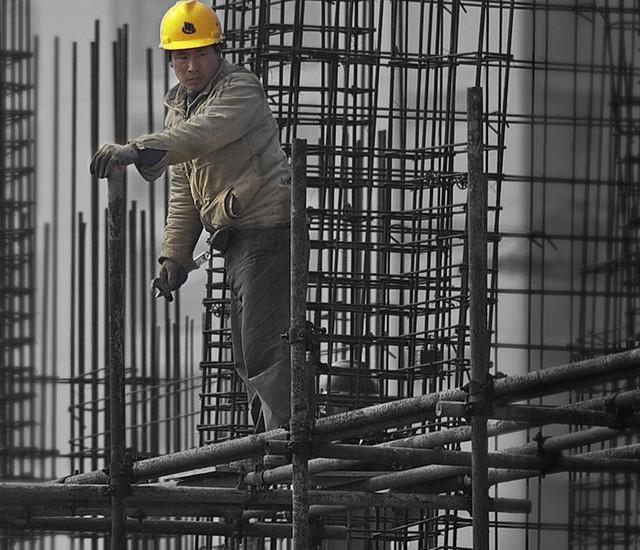 Строитель стоит на «лесах» высотного здания. Опытные инвесторы в недвижимость знают, что хорошие рыночные времена подходят к концу, когда люди с низким уровнем доходов становятся ключевыми целевыми покупателями. Фото: Dai Luo/flickr