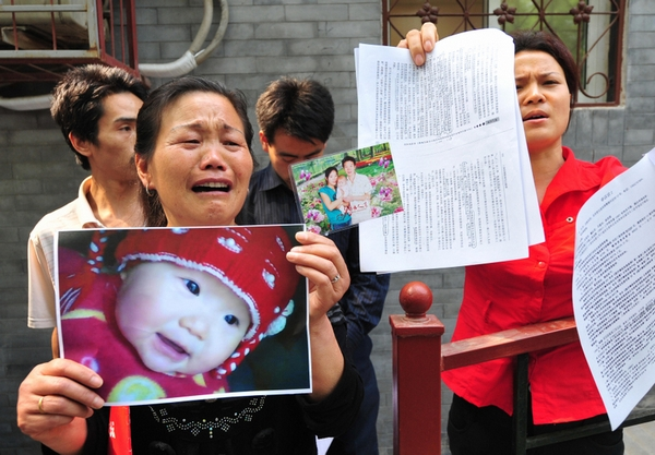 Zheng Shuzhen (L) holds a portrait of her deceased grand-daughter Zhou Mengxin while grieving outside the Complaints Department of the Ministry of Health in Beijing on May 8, 2009 claiming the child's death which resulted from the 2008 tainted milk scandal has never been dealt with appropriately by their local government in Zhoukou in Henan province. At least six babies died and nearly 300,000 fell ill in 2008 after they consumed milk powder contaminated by the industrial chemical melamine, which was mixed in to give the appearance of a higher protein content. The girl, who died on her birthday last June, had been fed Sanlu milk powder since the day she was born and never changed brands, said her father Zhou Fei, who tried to sue at the local court which refused to accept their case, resulting in the family's journey to Beijing in an attempt to reach a fair solution. The tainted milk scandal came to light in September after local authorities initially covered it up ahead of the Olympic Games, reviving long-standing fears over product safety in China and leading to recalls and bans around the world of Chinese-made products. AFP PHOTO / Frederic J. BROWN (Photo credit should read FREDERIC J. BROWN/AFP/Getty Images)