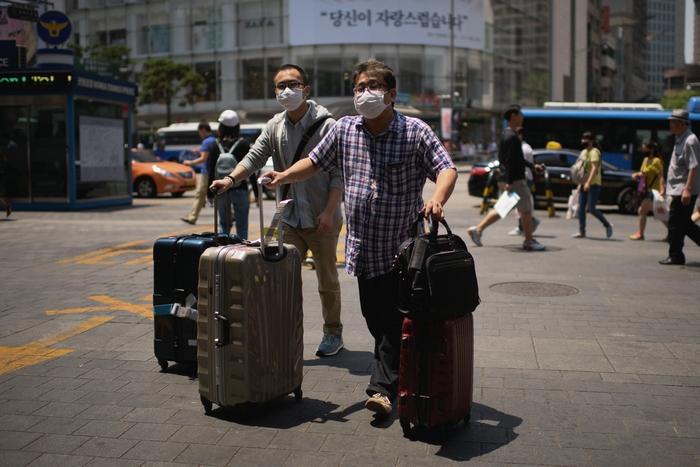 Туристы, застигнутые вспышкой вируса в Южной Корее, спешно покидают Сеул. Фото: ED JONES/AFP/Getty Images