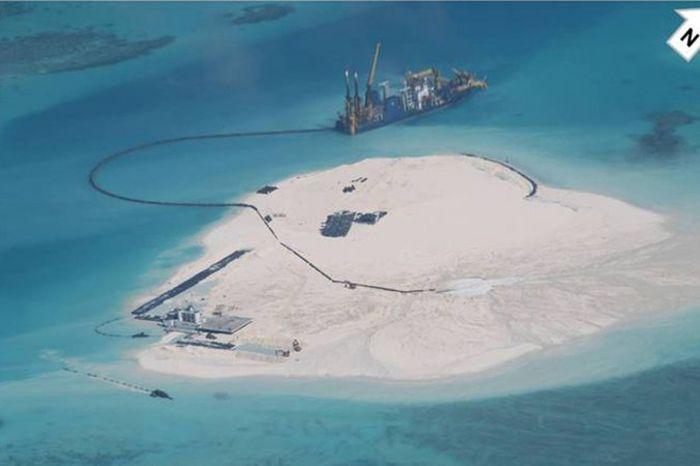 Китайский земснаряд намывает песок для увеличения исскуственного острова на рифе Джонсона, который в Филиппинах называют Мабини, а в Китае — Чигуа. Риф расположен в спорном районе островов Спратли в Южно-Китайском море. Снимок сделан 25 февраля 2014 Министерством иностранных дел Филиппин. Фото: МИД Филиппин.