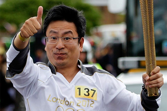 Ведущий телевизионного ток-шоу Бай Яньсун несёт Олимпийский огонь в Манчестере 23 июня 2012 года, Англия. Фото: Paul Thomas/Getty Images