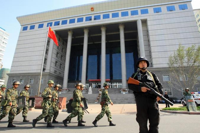 Китайские военные занимают позицию у здания суда в городе Урумчи, Китай. Фото: STR/AFP/Getty Images