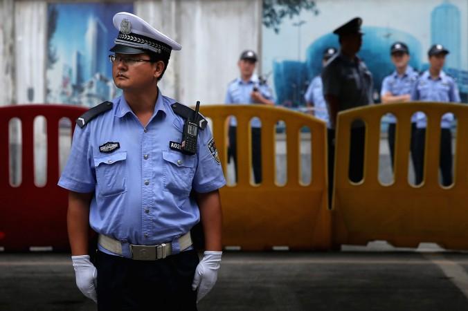 Китайские милиционеры охраняют вход в здание народного суда в Цзинане на четвёртый день судебного разбирательства в отношении бывшего члена Политбюро Бо Силая, 25 августа 2013 года, Китай. Фото: Feng Li/Getty Images