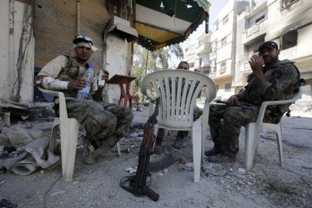 Soldiers of the Syrian government forces sit on plastic chairs in a devastated street on July 31, 2013 in the district of al-Khalidiyah in the central Syrian city of Homs. The Syrian government announced the capture of Khalidiyah, a key rebel district in Homs, Syria's third city and a symbol of the revolt against President Bashar al-Assad. AFP PHOTO/JOSEPH EID        (Photo credit should read JOSEPH EID/AFP/Getty Images)