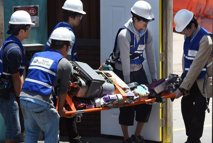 Спасатели уносят очередного робота, завалившего экзамен. Фото: MARK RALSTON/AFP/Getty Images