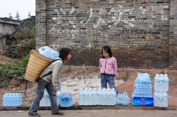 Китайские дети помогают переносить питьевую бутилированную воду в Цинлуне, провинция Юннань, 4 апреля 2010 г. Фото: STR/AFP/Getty Images