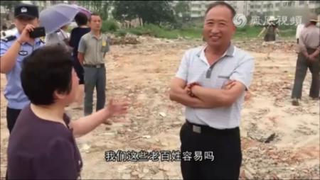 Китайский чиновник Хуа Гоцзюнь улыбается г-же Пань, дом которой только что снесли 18 июня 2015 года. Фото: скриншот/Phoenix Television