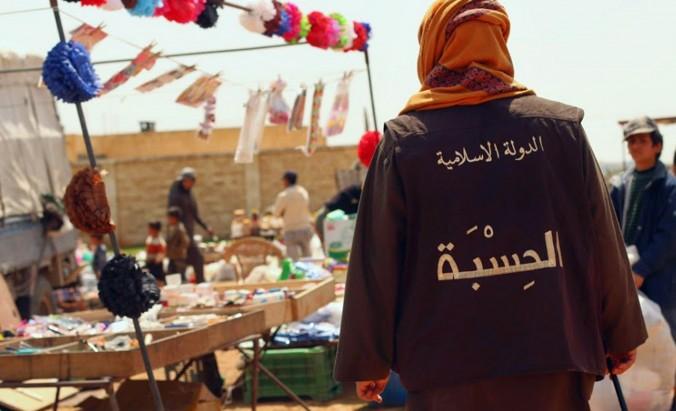 На этом фото, опубликованном 17 апреля 2015 года на сайте боевиков, показан полицейский «исламского государства» из группы, известной под названием «Хисба». Он патрулирует рынок города Ракка, Сирия. Арабские слова на жилете означают «Исламское государство — Хисба». Фото: theepochtimes.com