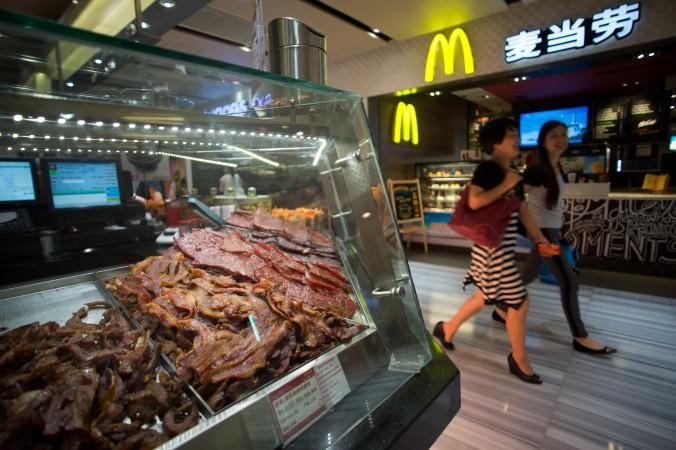 Люди проходят мимо ресторана «МакДональдс» в Шанхае 22 июля 2014 года. Фото: Johannes Eisele/AFP/Getty Images