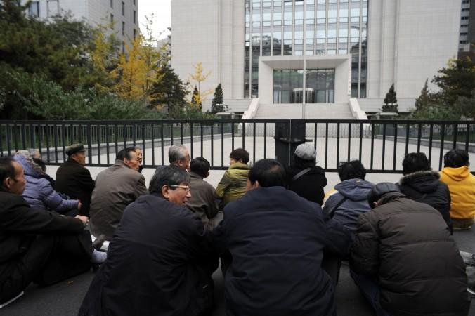 Группа пенсионеров, бывших работников тюрем в провинции Ляонин, проводит сидячую акцию протеста перед Министерством юстиции КНР в Пекине 8 ноября 2011 года. Они требуют погашения задолженности по пенсиям. Главой департамента юстиции провинции Ляонин до недавнего времени был Чжан Цзячэн. С его ведома в тюрьмах провинции многие узники совести были подвергнуты пыткам и жестокому обращению. Фото: Goh Chai Hin/AFP/Getty Images