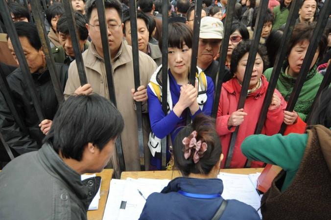 Люди стоят в очереди, чтобы попасть в список на получение новых квартир после того, как местные власти объявили о сносе старого здания в центре района Тунчжоу, Пекин, 8 апреля 2010 года. Фото: STR/AFP/Getty Images