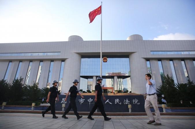 Полицейские патрулируют около здания промежуточного суда в Куньмине, столице провинции Юньнань, 12 сентября 2014 года. Фото: STR/AFP/Getty Images