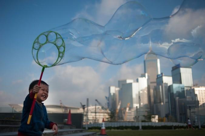 Мальчик надувает мыльный пузырь, Гонконг, 22 ноября 2014 года. Фото: Photo by Anthony Kwan/Getty Images