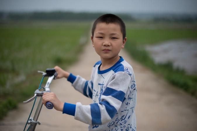 Мальчик, родители которого уехали на заработки, деревня Чжуаншуцзуй провинции Хунань, 30 апреля 2013 года. Фото: Ed Jones/AFP/Getty Images