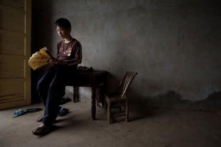 Мальчик, родители которого уехали на заработки, рассматривает веер, деревня Чжуаншуцзуй, провинция Хунань, 30 апреля 2013 года. Фото: Ed Jones/AFP/Getty Images