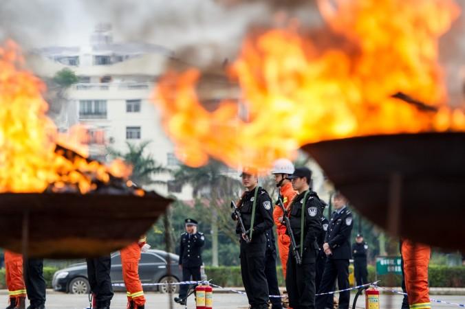 Полицейские наблюдают за уничтожением наркотиков в уезде Нинмин округа Чунцзо 10 марта 2014 года, Китай. Фото: STR/AFP/Getty Images