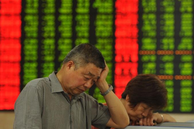 Инвесторы проверяют стоимость акций в фондовой компании города Фуян провинции Аньхой 26 июня 2015 года. Фото: STR/AFP/Getty Images
