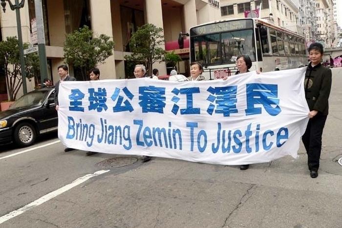 Надпись на плакате: «Привести к суду Цзян Цзэминя». Фото: The Epoch Times