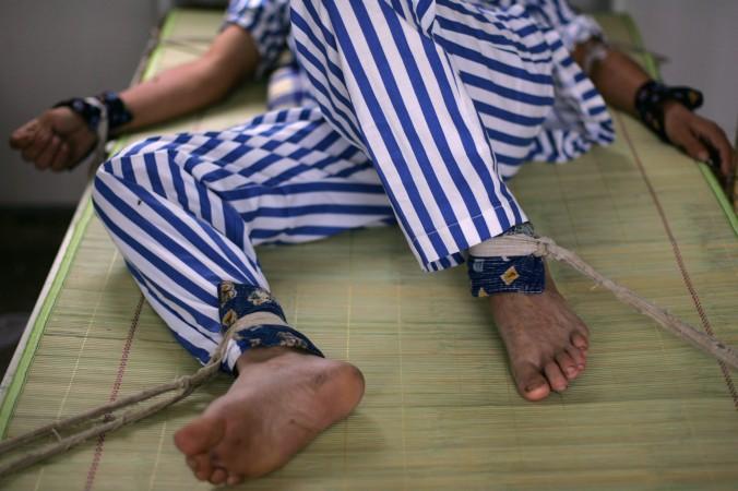 Пациент лежит в постели с привязанными руками и ногами в психиатрической больнице уезда Аньсянь провинции Сычуань 24 августа 2008 года. Фото: China Photos/Getty Images