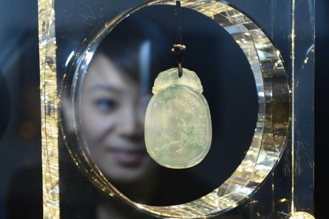 Женщина рассматривает ювелирное изделие на международной ювелирной выставке в Пекине 16 декабря 2012 года. Фото: STR/AFP/Getty Images