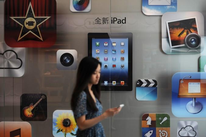 Покупательница проходит мимо магазина Apple в Шанхае, 2012 г. Новый китайский закон о кибербезопасности создаст трудности для таких компаний, как Apple, и для китайской экономики. Фото: Peter Parks/AFP/Getty Images