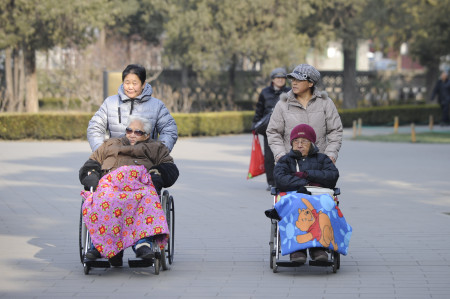 Two elderly people are pushed on their wheelchairs at a park in Beijing on December 11,2012. China's elderly face increasing uncertainty three decades since the one-child policy took hold, with no real social safety net, the law has left four grandparents and two parents with one caretaker for old age -- and bereaved families with none.       AFP PHOTO/WANG ZHAO        (Photo credit should read WANG ZHAO/AFP/Getty Images)