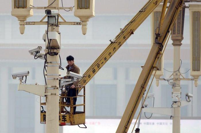 Человек проверяет камеры наблюдения на площади Тяньаньмэнь в Пекине 31 октября 2013 года. Китайская компартия создаёт базу данных на американцев, используя программу, при помощи которой она следит за своими гражданами. Фото: Ed Jones/AFP/Getty Images
