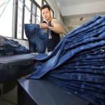 Китайский рабочий изготавливает джинсы на фабрике в Шиши, провинция Фуцзянь. Фото: STR/AFP/Getty Images