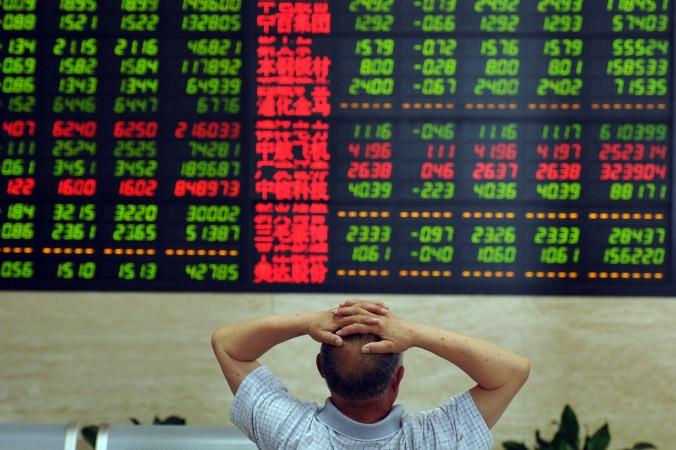Работник биржи смотрит на курс акций, г. Фуян, провинция Аньхуэй, Китай, 19 июня 2015 г. Фото: STR/AFP/Getty Images