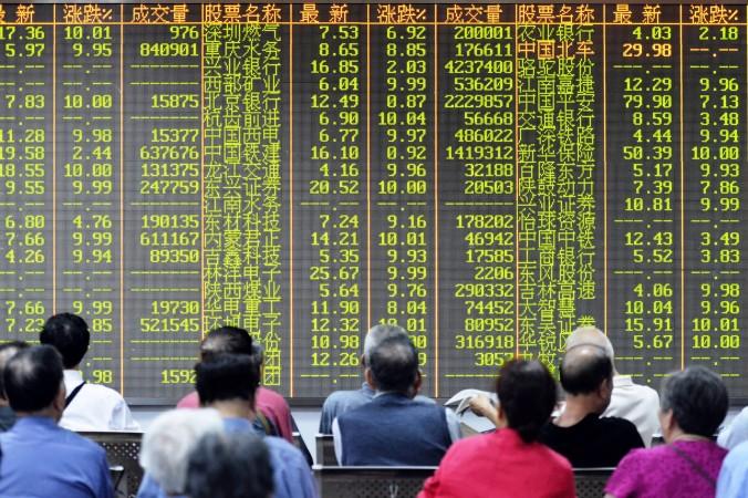 Шанхайская и Шэньчжэньская биржи за три недели упали более чем на 30%. На фото инвесторы сидят перед экраном с котировками акций в Ханьчжоу, провинция Чжэцзян, 8 июля 2015 года. Фото: STR/AFP/Getty Images
