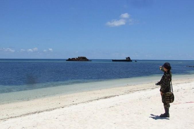 Военнослужащий стоит на пляже острова Тхиту, на котором находится небольшой филиппинский город, а также взлетно-посадочная полоса, используемая для гражданских и военных полётов на спорные острова Спратли в Южно-Китайском море. июнь, 2014 год. Фото: STR/AFP/Getty Images
